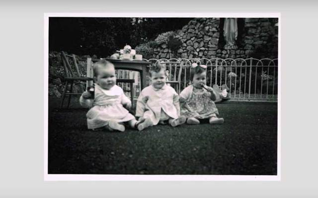 Black-and-white photograph of three infants sitting on a lawn.