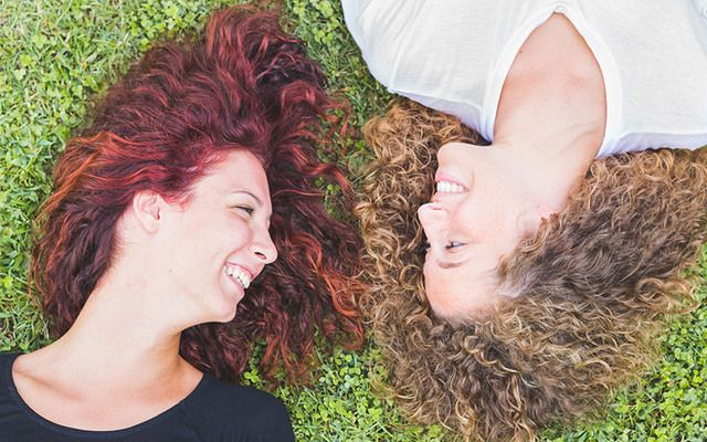 Redhead women lying on the grass.
