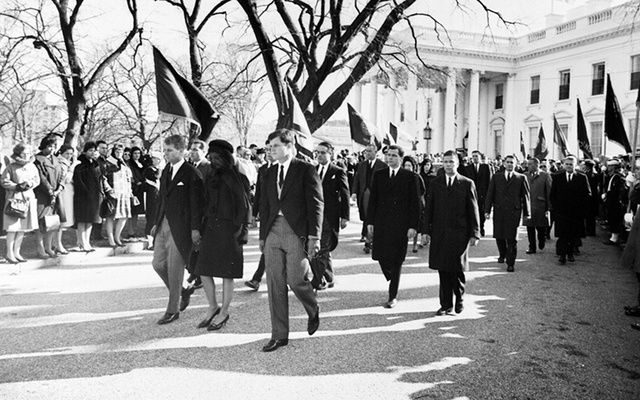 Photograph of Jacqueline Kennedy, accompanied by her brothers-in-law, Attorney General Robert F. Kennedy and Senator Edward Kennedy, walking from the White House as part of the funeral procession accompanying President Kennedy\'s casket to St. Matthew\'s Cathedral.