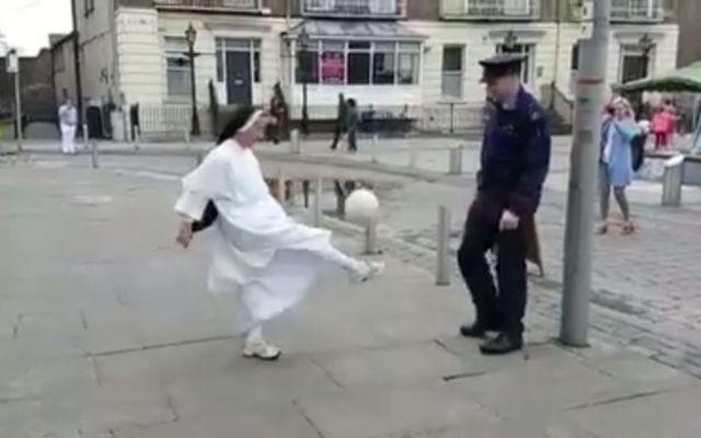 Look at that kick! Nun and cop play soccer.