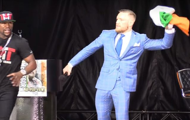MMA champ Conor McGregor throwing the Irish flag to the ground at Floyd Mayweather's feet.