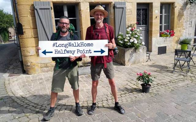 Eamonn Donnelly (left) and Sepp Tieber hold up a sign saying #LongWalkHome Halfway Point.