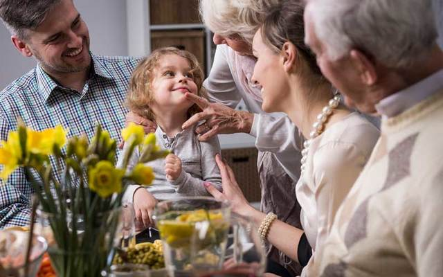 A happy three-generation family smile at a young child around a dinner table.