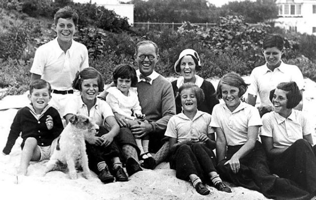 "September 4, 1931: The Kennedy Family at Hyannis Port. L-R: Robert Kennedy, John F. Kennedy, Eunice Kennedy, Jean Kennedy (on lap of) Joseph P. Kennedy Sr., Rose Fitzgerald Kennedy (who was pregnant with Edward ""Ted\"" Kennedy at time of this photo), Patricia Kennedy, Kathleen Kennedy, Joseph P. Kennedy Jr. (behind) Rosemary Kennedy. The dog in the foreground is Buddy."