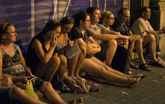 Witnesses look on after the terror attack in Barcelone yesterday in which at least 13 people died.