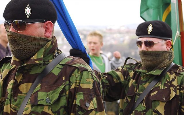 Irish Republican Army members march, wearing a lily in their hates to remember fallen combatants.