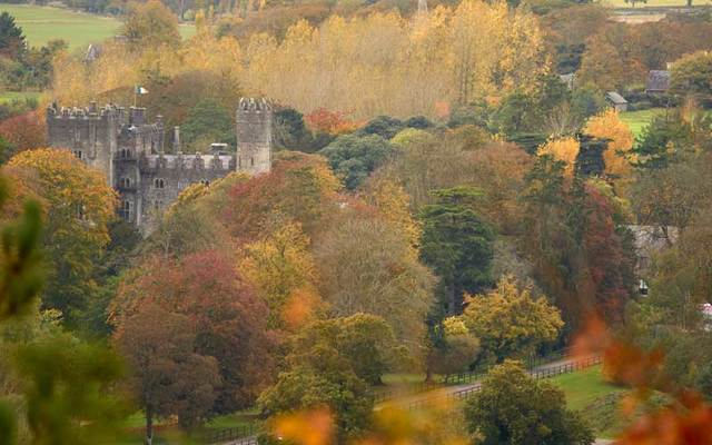 An Irish castle amidst woodland in autumn.