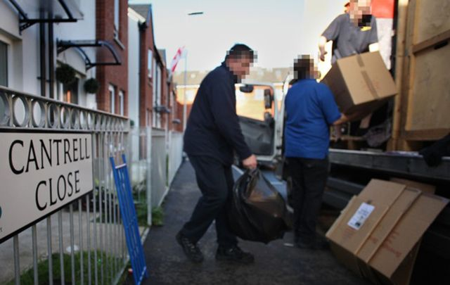 A Catholic family moves possessions from their home in Cantrell Close in Belfast. The faces have been obscured in the photo for the family's protection.