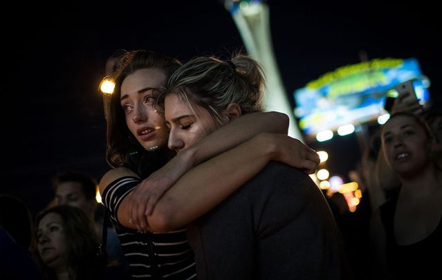 Survivors huddle in the wake of the murder of 59 people and shooting of over 100 others.