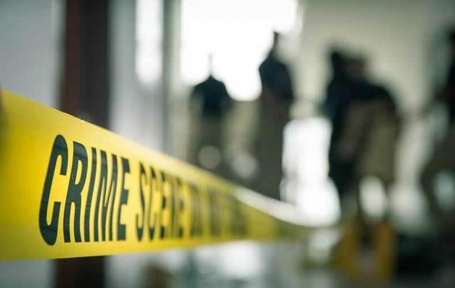 Crime scene tape with blurred investigators in background.