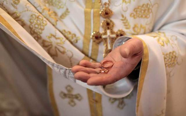 A priest holds wedding rings in his hand.
