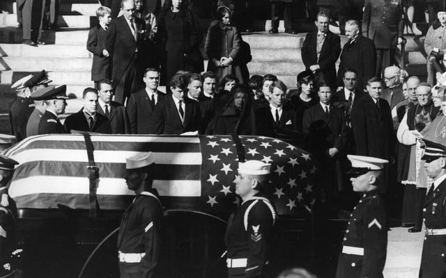 Jacqueline Kennedy, Edward Kennedy and Robert Kennedy stand as the coffin of President John Fitzgerald Kennedy passes them
