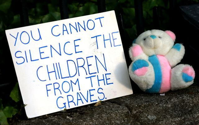 """A sign posted in front of Ireland\'s government building in protest of the Tuam babies mass grave - \""""You cannot silence the children from the graves.\"""""""