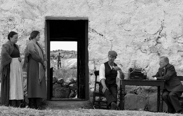 A scene from Song of Granite in which a young Joe Heaney watches as his father sings for a folklore collector.