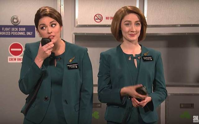 Screen shot of Aer Lingus skit on SNL, with Cecily Strong and Saoirse Ronan as flight attendants.