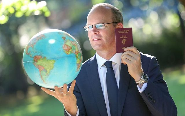 Minister for Foreign Affairs and Deputy Leader Simon Coveney poses with an Irish passport and a globe.