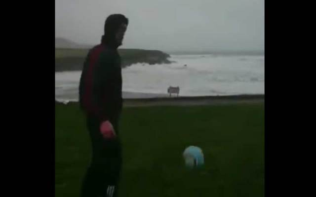 Irish football player Eanna O'Connor kicks a ball out into the weather and the strong winds send it right back to him.