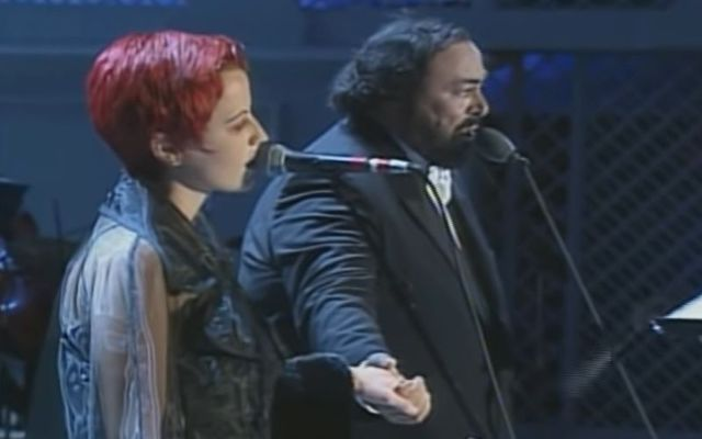 """Luciano Pavarotti kisses Dolores O\'Riordan\'s hand after performing \""""Ave Maria\"""" in Modena, Italy, in 1995."""