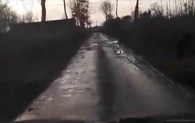 Horrible Irish road filled with potholes and water.