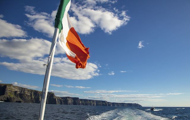 Scenic view of the Cliffs of Moher, Liscannor, Ireland, with the Irish flag tricolor.