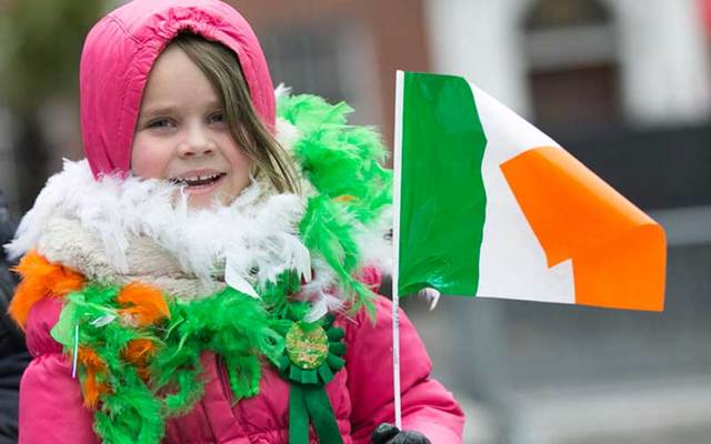 A little girl bundled up in the cold for St Patrick\'s Day celebrations.