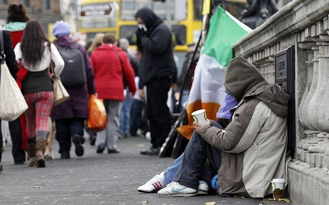 A homeless couple begging on O\'Connell Bridge, Dublin.