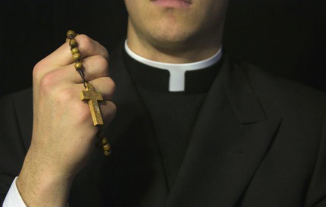 A Catholic priest holding rosary beads.