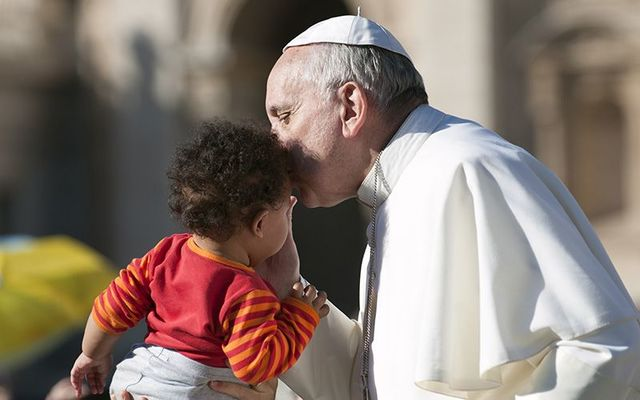 Pope Francis kissing a baby during a public visit.