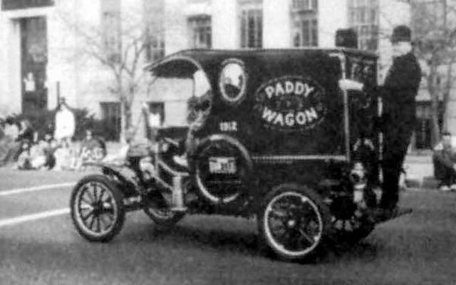 """Black-and-white photo of a policeman standing on the back of vehicle, which has the words \""""Paddy Wagon.\"""""""