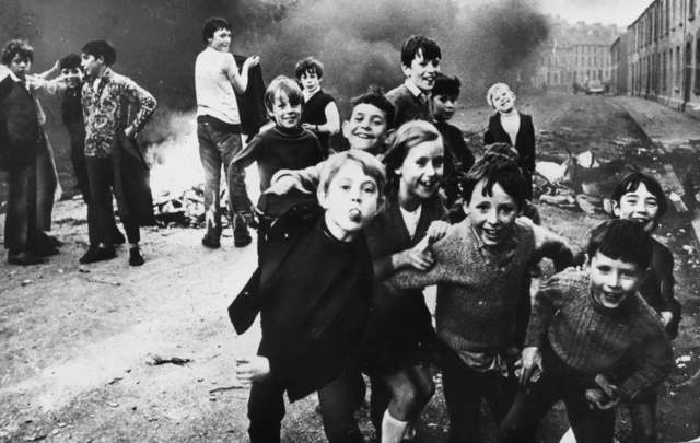 7th December 1971: Children jeer at British soldiers while a fire smolders in the street behind them.