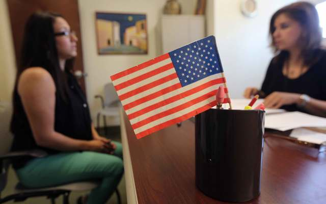 Colombian immigrant Paola Parra (L) takes her oral citizenship test at the U.S. Citizenship and Immigration Services (USCIS) Queens office on May 30, 2013, in the Long Island City neighborhood of the Queens borough of New York City.