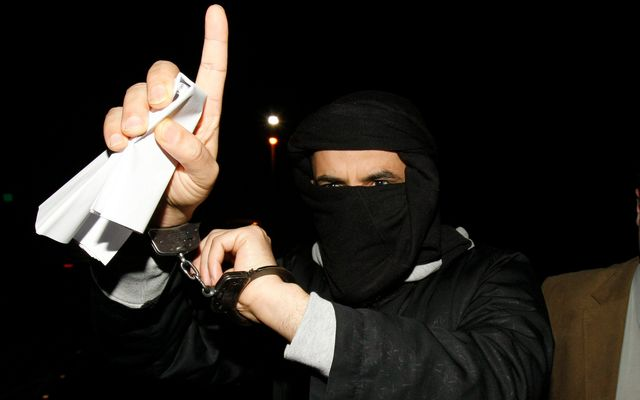 Ali Charafe Damache (L) of Algeria arrives with Irish Police to the Waterford District Court in Waterford, Ireland on March 15, 2010, after being charged. Damache was one of two men in custody in connection with an alleged plot to murder cartoonist Lars Vilks over a picture of the Prophet Mohammed with the body of a dog.