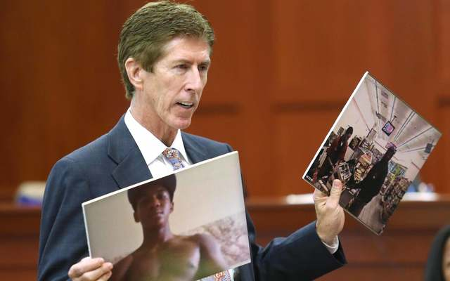Mark O\'Mara displays photos of Trayvon Martin to the jury during closing arguments in Zimmerman\'s murder trial July 12, 2013, in Sanford, Florida.\n