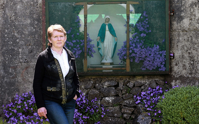 Amateur historian Catherine Corless standing in front of a shrine, built by locals, on the site where 796 children were buried in a mass grave in Tuam, Galway.