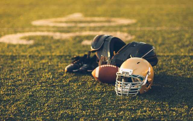 A Gold American Football helmet sits with a football on a football playing field.