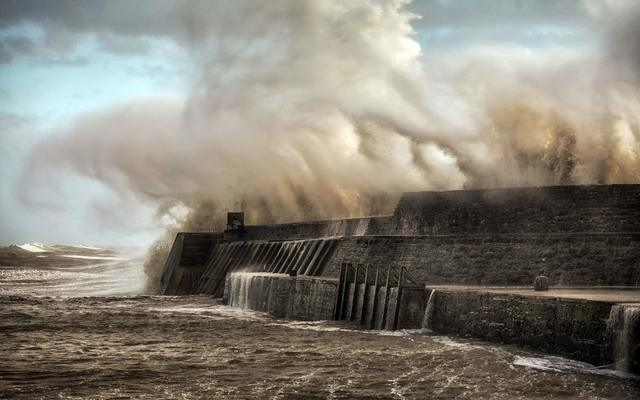Porthcawl lighthouse and pier in the jaws of Storm Ophelia as the hurricane hits the coast of South Wales, UK.\n