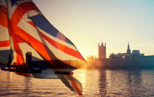 British union jack flag and Big Ben Clock Tower and Parliament house at the city of Westminster in the background.