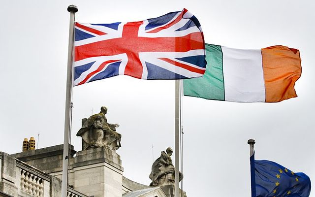 The Union Jack flag and the Irish tricolor flag flying above Stromont, Northern Ireland\'s government buildings.