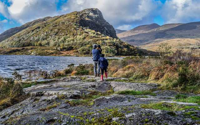 A family with a dad and young daughters looks out to an idyllic and incredible view in Killarney, Ireland.