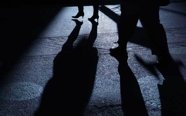 A man follows a woman on a dark street.