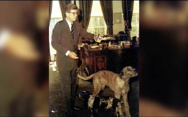 President John F. Kennedy in the Oval Office with two of his dogs.