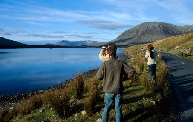 A small group of people is standing on the roadside to gaze at the astonishing scenery of Connemara in Ireland.