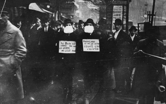 Two men wearing and advocating the use of flu masks in Paris during the Spanish flu epidemic which followed World War I.
