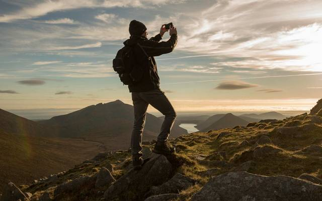 Hiker photographing Mourne Mountains, Northern Ireland.\n