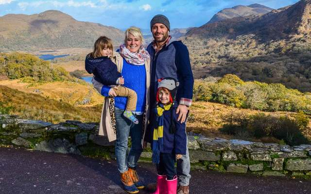 A snap of a young family with two children posing in front of Lady\'s View, a scenic and beautiful valley in Ireland, within the Ring of Kerry. \n