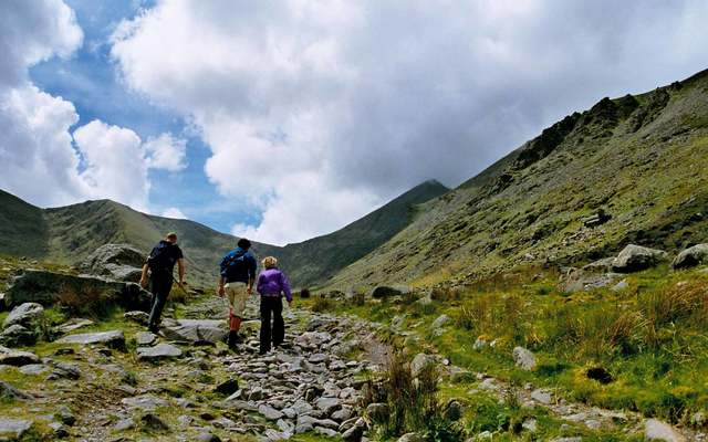 Three people climbing the highest mountain in Ireland, Carrauntoohil in County Kerry. \n
