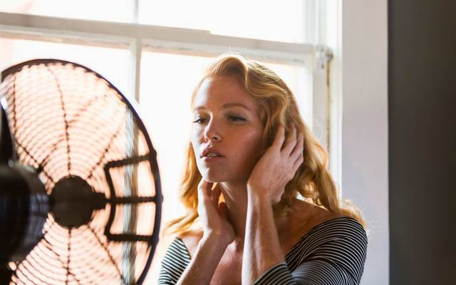 A woman trying to cool off in front of an electric fan.