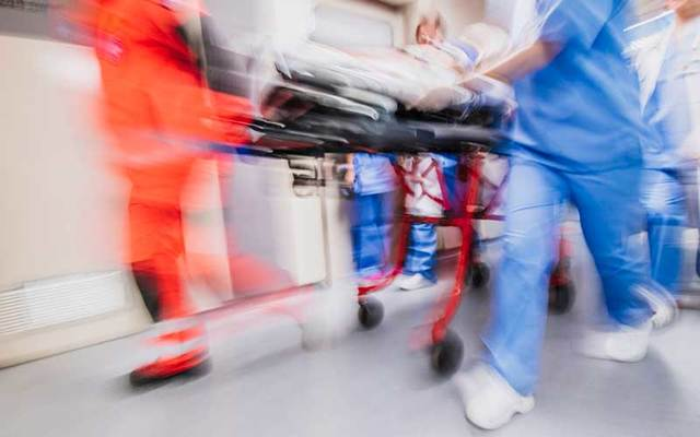 Paramedics and nurses pull hospital trolley in an ER.