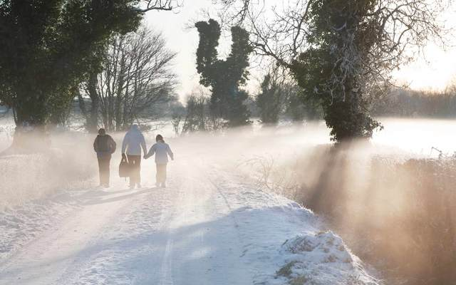 A mother bringing her two children to school on foot on a frosty winter morning.