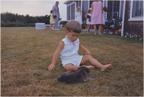 A very young John F Kennedy Jr plays with a puppy on the Kennedy compound at Hyannisport, in Cape Cod.